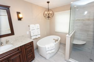 Close-Up-Of-Bathtub,-Glass-Shower-Doors,-and-Detailed-Gray-Tile-Of-Step-In-Shower